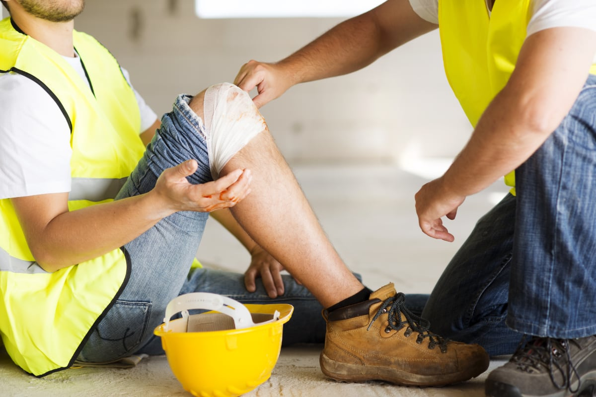A worker sitting wearing a high visibility vest looking at bandaged knee