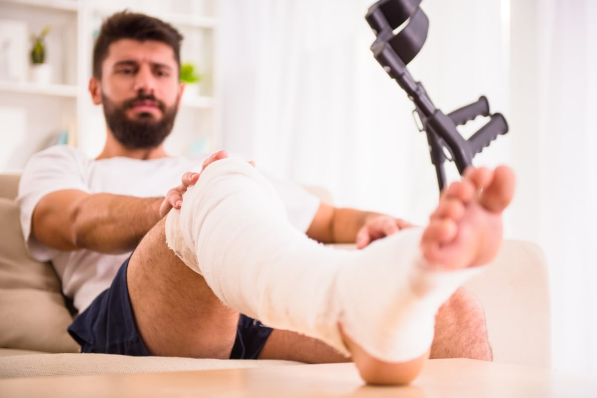 Man sitting on chair with leg in a cast