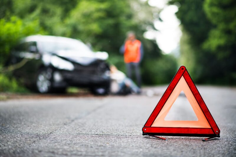 orange triangle hazard sign in foreground with car smashed in background