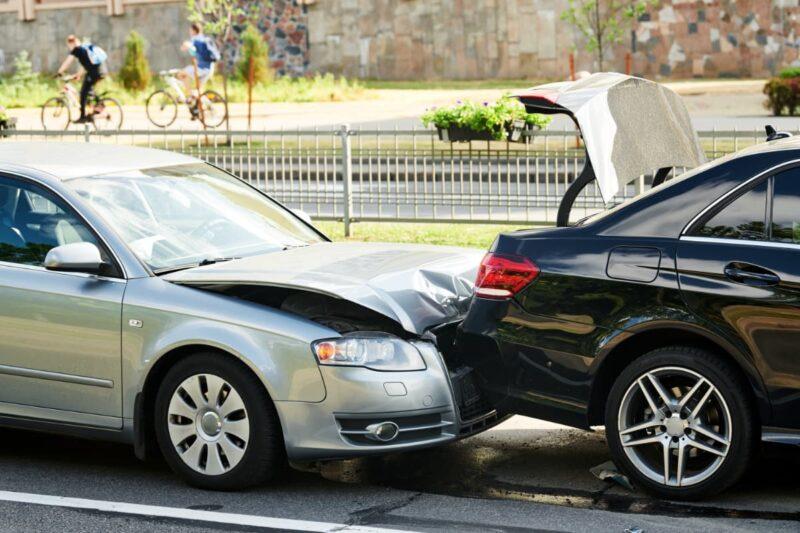 silver car with front end smashed under black cars back end
