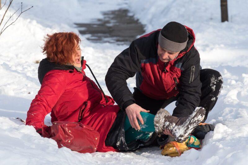 man helping woman in red winter coat down on icy sidewalk