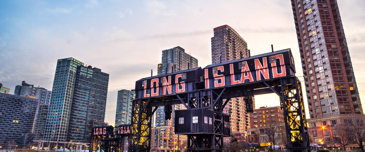 Large painted lettering spelling out Long Island in front of some taller buildings