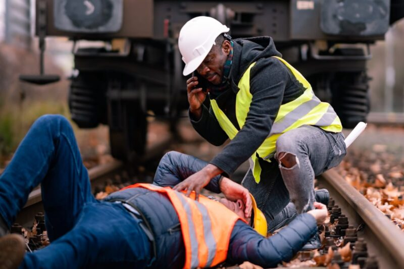 construction worker on phone while kneeling over coworker lying on train tracks