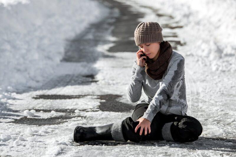 woman sitting on icy sidewalk holding leg while on phone